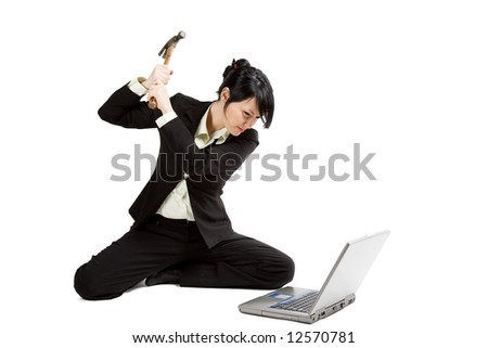 An isolated shot of an angry and stressed businesswoman smashing her laptop with a hammer