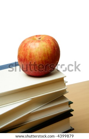 An isolated shot of an apple on top of a pile of books
