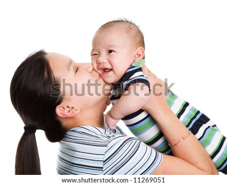 An isolated shot of an asian mother kissing her baby son