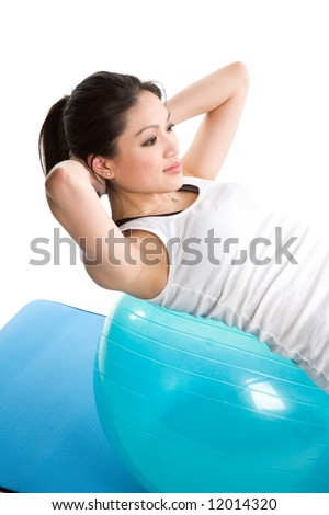 An isolated shot of an asian woman doing sit-up on an exercise ball