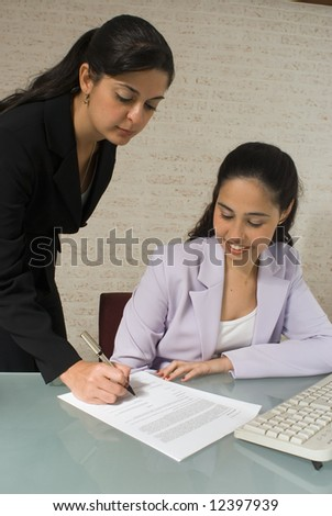 An isolated shot of two businesswomen signing a contract.