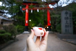 an isolated travel tourist hand holding a small pink rabbit clay doll figure souvenwith a blurred background of a red torii gate in front of the Ujigami jinja shrine in Kyoto, Japan with sombre mood.