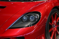An isolated view of the left front of a red sports car.