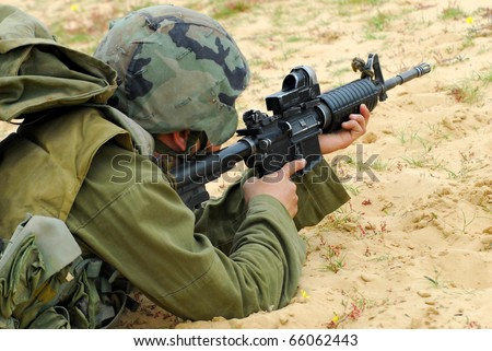 An Israeli defense forces soldier dressed in uniform aims his M16 rifle while on duty. Concept photo of war ,military, army, armed forces, incursion,conflict ,firearm ,battle, attack.