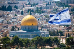 An Israeli flag blows in the wind from the mount of olives overlooking the old city of Jerusalem, Israel. Jerusalem is the most visited city in Israel with 3.5 million tourist arrivals annually.