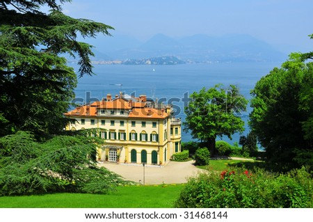 an Italian mansion or (palazzon) on lake maggiore set in ornamental park land with a stunning view of the lake and the italian alps in the distance