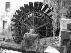an italian water mill in black and white