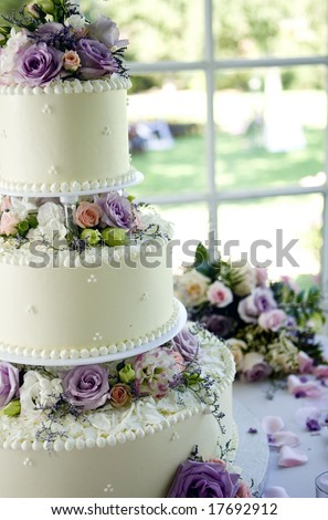An ivory wedding cake with roses in the window - stock photo