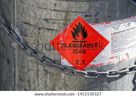 An LPG tank secured with a strong chain and showing a Flammable Gas 2.1 sign