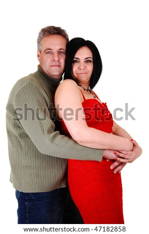 An middle age couple, she in an red dress and black hair and her husband gives her a big hug, standing on his side, on white background.