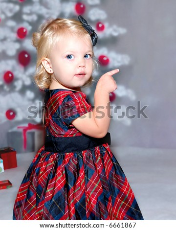 an 18 month old toddler girl child standing in front of the christmas tree in her