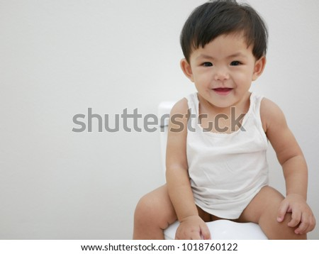 An 11 months old Asian baby sit on a baby-size toilet for a toilet training