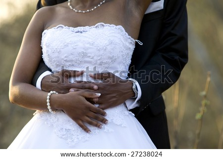 An newly-wed African-American couple holding each other
