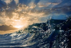 An ocean sunset shorebreak in side view with bokeh flares. Big beautiful high contrast sunrise wave swirling. Bright sun shining on blue sky with colorful clouds.