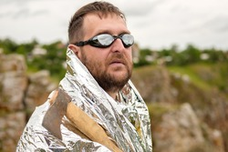 an oddball in glasses with an axe in his hand and dressed in foil against the sky. strange man