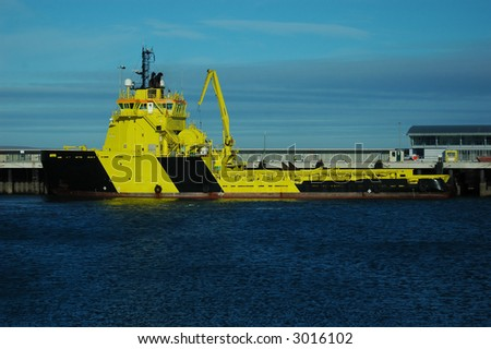 An off shore supply or support vessel berthing at the pier. - stock photo
