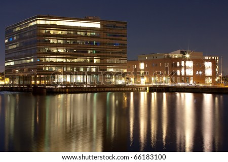 An office building by the harbour at night - stock photo