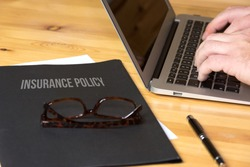 An office, computer and a folder with insurance policy
