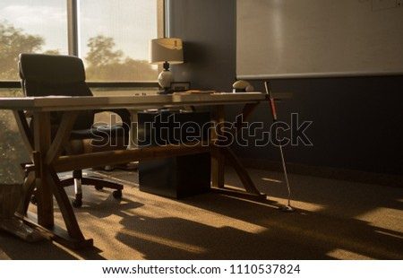 An office interior with a golf putter leaning on a desk at sunset/magic hour.