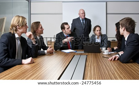 An office meeting between a senior executive and six of his junior staff members - stock photo