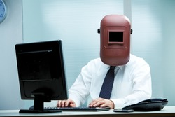 An office worker at his desk wearing a welder's mask