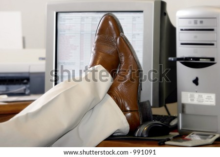 An office worker puts his feet up on his desk and ignores the computer work to be done.