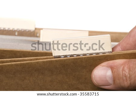 An office worker sorts through files.  Copy space is left on the file tabs for designers to insert their own message.