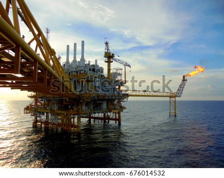 An offshore oil and gas installation and a platform supply ship at sunset time.