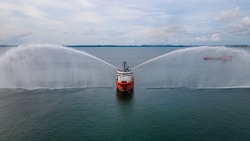 An offshore support vessel testing her fire fighting system to ensure readiness of the system whenever required to be used in an emergency.