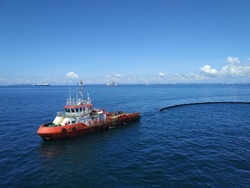An offshore vessel performing oil spill response exercise in the middle of the sea. Oil spill response comprises of mother boat and a tow boat to carry oil spill boom.
