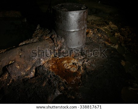 An oil drum stands amongst carcinogenic crude oil pollution produced by illegal oil mining in East Java, Indonesia.