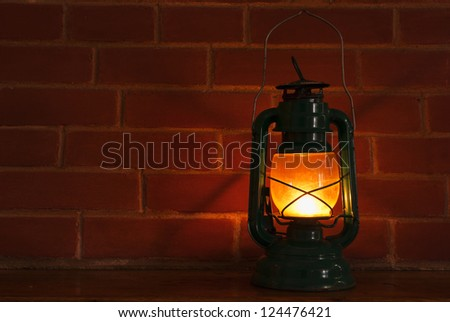 An oil lamp lantern lighting in front of a brick wall background.