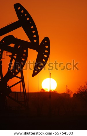 An oil pump jack is silhouetted by the setting sun