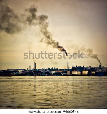 An oil refinery polluting the atmosphere with a huge smoke column pictured at sunset