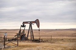An oil well pump jack pumping on the prairie of Oklahoma during a cloudy day.