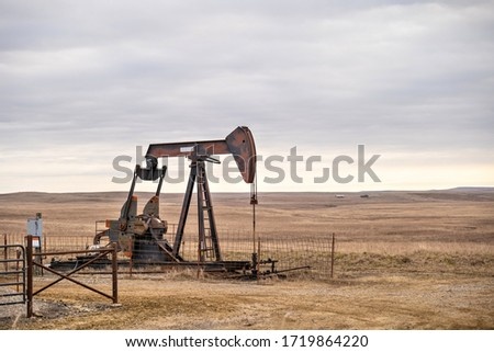An oil well pump jack pumping on the prairie of Oklahoma during a cloudy day. Stockfoto ©
