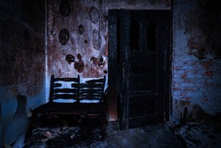 An old abandoned and burned out building with ruined furniture bed chairs