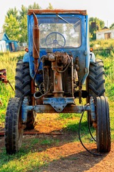 An Old abandoned Antique Tractor in village or Farm Country. The tractor is covered with rust. Agricultural machinery. Rural landscape. Summer village.