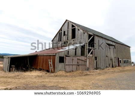 An old abandoned barn. There are holes and missing pieces in the walls. Overcast sky.
