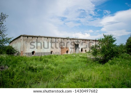an old abandoned building located on a green grass field.  Former warehouse of fruits and vegetables in the 1980s. Holes in the walls- brick construction. a beautiful blue sky with many fluffy clouds. stock photo