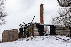 An old abandoned charred building in snowy hill. After accident with fire burnt wooden walls and red brick chimney are all what is left from home at grey winter day