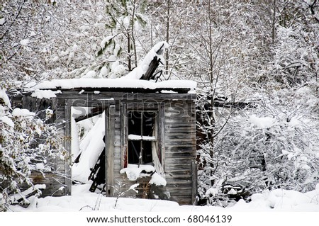 An old abandoned collapsed building covered in a winter snow storm