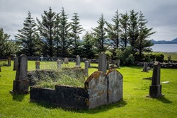 An old, abandoned double grave in the cemetery, surrounded by smaller tombs.  Green grass, trees in background.