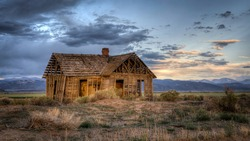 An old abandoned farmhouse on the Great Plains at Sunset