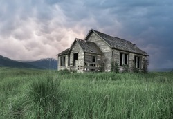 An Old Abandoned House in Green Grass Field with Dramatic Dark Clouds