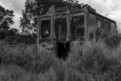 An old abandoned house, somber, scary and spooky with the grass grown and a darkness ready to receive those who dare to enter, a  haunted place in ruins of a past of disaster, death and ghosts wait.