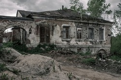 An old abandoned house with an arch stands on the street