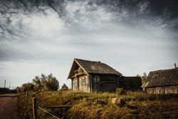 An old, abandoned log house. Deserted village in Russia. A lonely hut without people. Rotten wall construction. Hut against the background of the blue sky. Karelia. Russia. Day.