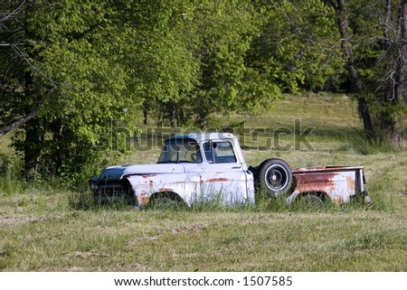 An old abandoned pickup truck sitting in a grassy field. - stock photo