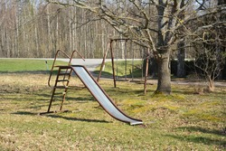 An old abandoned playground. Rusty swing and slide.